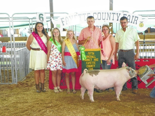 Caleb Penwell's hog was named fifth place overall on Wednesday at the Fayette County Junior Fair Market Hog Show. Penwell is pictured with Fair Queen Abbie Noble, Fair Attendant Alyssa Backenstoe, Fair Attendant Taylor Kirkpatrick, Pork Queen Caroline Hughes, and judge Miles Toenyes.