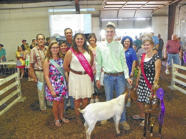 Riley Evans' Grand Champion Meat Goat sold for $1,500 on Wednesday evening at the Fayette County Junior Fair Boer Goat Sale. Pictured with Evans are fair royalty and buyers: (first row) Small Animal Queen Ginna Climer, Fair Queen Abbie Noble, Goat Ambassador Virginia Schappacher; (second row) Phil Grover of Maple Grove Farms, Drew Pontious, Washington C.H. Municipal Court Judge Victor Pontious, Carol Pontious, Diane Faris of Faris Insurance, and Debbie Cokonougher of EZ Oil.
