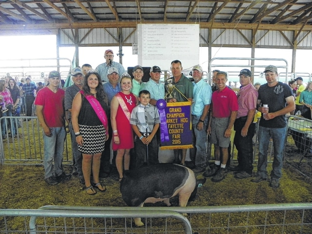 Grayson Keller's Grand Champion Hog sold for $4,000 on Thursday evening at the Fayette County Junior Fair Hog Sale. Keller is pictured with fair royalty and buyers: (first row) Fair Queen Abbie Noble, Pork Queen Caroline Hughes, Scott Baird of OK Tire, (second row) Jamie Payton, Caleb Penwell, Rusty Coe of Coe Farms, Jon Wilt of Patchwork Gardens, Brock Wilt of New Generation Showpigs, Bryan McCoy of Beck's Hybrids, Jim Worley of Worley Pigs, Jim McCoy of Real McCoy, Jamie May of May Hogs, Jeff Wilt of Aluminum Works, and Mark Hughes of Vermeer Heartland.