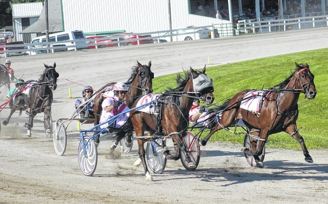 Horses make the turn during the first of 12 races at the Fayette County Fair Wednesday, July 22, 2015. There will be a card of 13 races Saturday, beginning at noon and culminating with the Fayette County Classic.