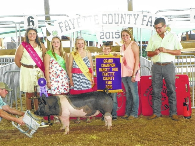 Grayson Keller's hog was named grand champion on Wednesday at the Fayette County Junior Fair Market Hog Show. Keller is pictured with Fair Queen Abbie Noble, Fair Attendant Alyssa Backenstoe, Fair Attendant Taylor Kirkpatrick, Pork Queen Caroline Hughes, and judge Miles Toenyes.