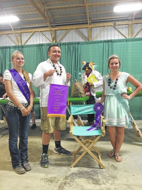 Zach Potts (pictured center) was named overall showman in the turkey category Monday night. Fair Attendant Emily Daniels (left) and Small Animal Queen Ginna Climer (right) presented Potts his chair and ribbon.