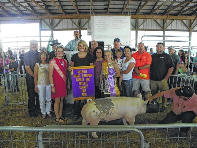 Brooklyne Baldwin's Reserve Champion Hog sold for $2,000 on Thursday evening at the Fayette County Junior Fair Hog Sale. Baldwin is pictured with fair royalty and buyers: (first row) Tracy Ross of Four Seasons, Pork Queen Caroline Hughes, Diane Faris of Faris Insurance, Fair Attendant Taylor Kirkpatrick, Janelle VanDyke of Buckeye Propane, Shawn Long of Agriline, (second row) Fayette County Commissioner Dan Dean, Fayette County Sheriff Vernon Stanforth, Karen Cassidy of First State Bank, Max Hughes of Gusweiler, Jared Hoop of Baxla Tractor, and Duane Litteral of Sugar Creek Packing.