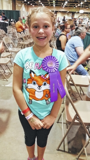 """Hayleigh Bageant took """"Outstanding of the Day"""" in the You and Your Dog Interview Project at the 2015 Ohio State Fair. Hayleigh was chosen to represent Fayette County in her age group at the Ohio State Fair. Hayleigh enjoyed training her dog Levi and working hard on her poster and interview questions. """"I had a blast this year! It was very exciting and I never thought that I would get to go to the Ohio State Fair with my poster. Levi and I are ready for 4H next year,"""" said Hayleigh. She is the daughter of Danyel and Tim Bageant."""