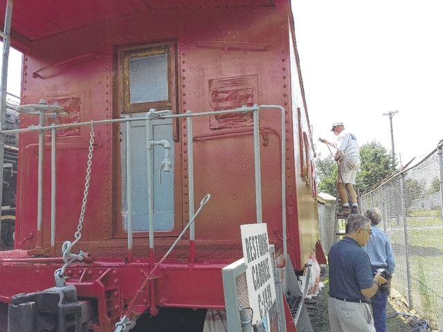 The Railroad Preservation Society of Fayette County has started painting the historic caboose that adorns Eyman Park recently with a sleek red finish. They are seen here Tuesday afternoon applying the second coat of paint.