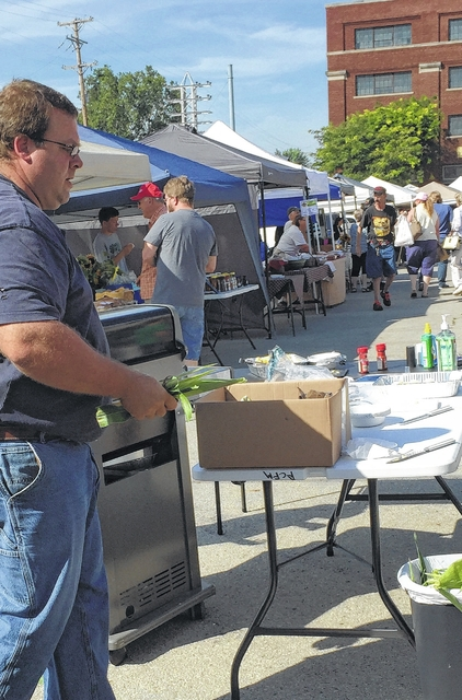 Kevin shucking corn for the corn grilling and tasting at the Fayette County Farmers Market.