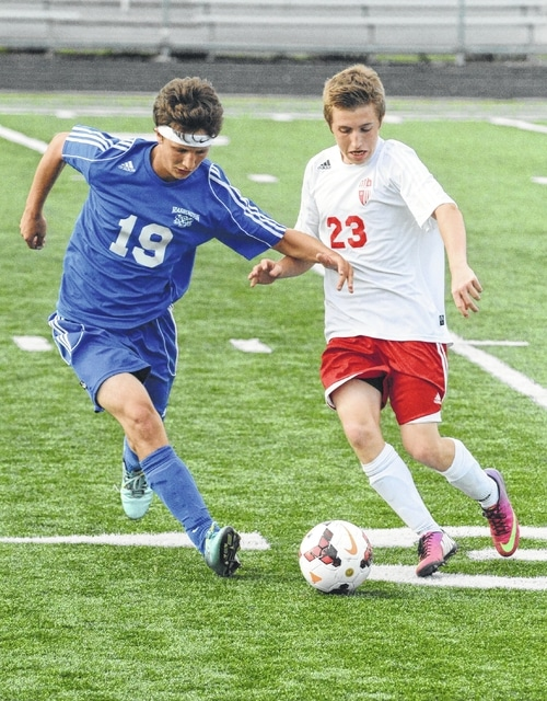 Washington's Jacob Snyder (19) looks to deny a Clinton-Massie player from controlling the ball during an SCOL match at Clinton-Massie High School Tuesday, Aug. 25, 2015.