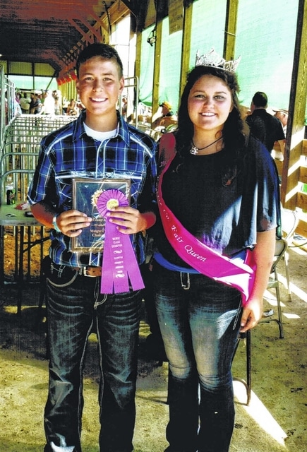 Tyler Eggleton, a class winner in the 2015 Fayette County Junior Fair Market Hog Show, is pictured here with the 2015 fair queen Abbie Noble.