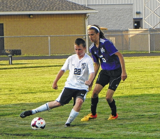 Miami Trace freshman, Drew Batson (22), keeps the ball away from a McClain Tiger player during their match-up Thursday, Sept. 3, 2015 at Miami Trace High School.