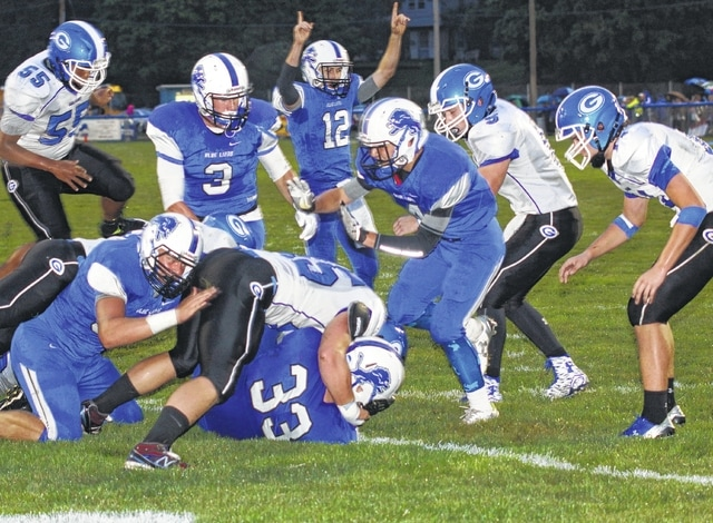 Aaron Greer (33) makes it over the goal line for a touchdown on the opening drive for the Washington Blue Lions in their Homecoming game against Gallia Academy Friday, Sept. 11, 2015. Players pictured for Washington (l-r); Trevor Hicks, Timothy Robinson (3), C.J. Taylor (12) and Caleb Rice.