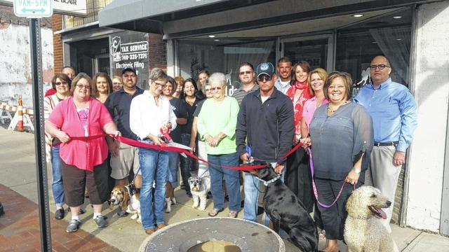 Good Dog Groomery owner, Jackie Roberts, cuts the ribbon on her new downtown location with help from the Chamber of Commerce and several two-legged and four-legged friends.