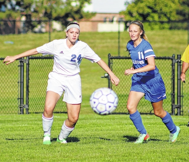 The Washington Lady Blue Lion soccer team hosted Clinton-Massie for an SCOL match Thursday, Sept. 17, 2015. Massie won the match, 11-0. Above, Washington's Kara Foy (24) and a player from Clinton-Massie keep their eyes on the ball on a sun-drenched late summer evening.
