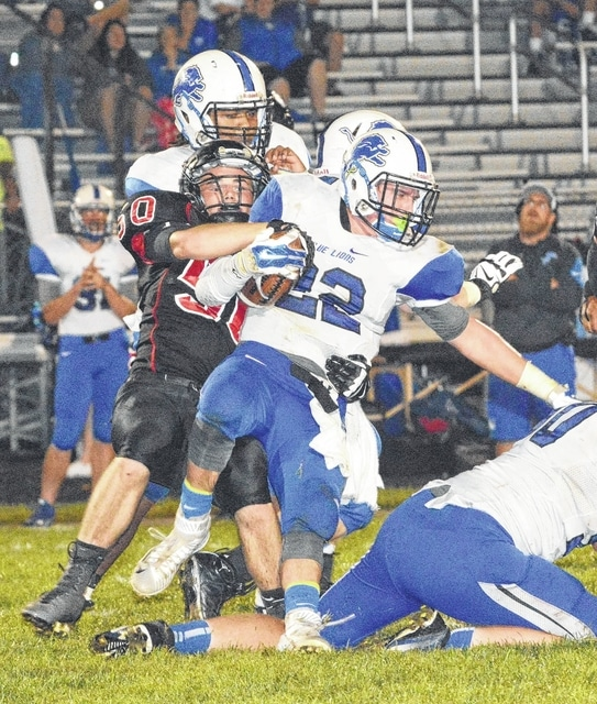 Washington Blue Lion senior Timothy Robinson (22) is wrapped up by Circleville's Mike D'Aiello during a non-league game at Circleville High School Friday, Sept. 4, 2015.