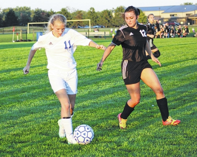 Cassy Hart (left) has the ball for Washington, defended by Makayla Eggleton of Miami Trace during an SCOL match at Washington High School Tuesday, Sept. 15, 2015.