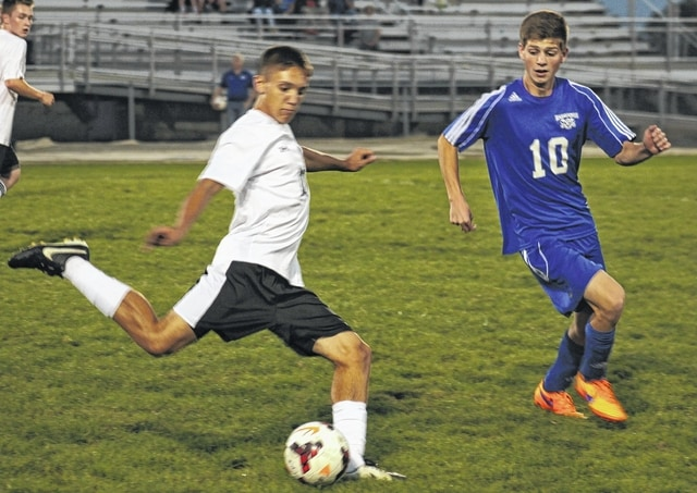 Miami Trace's Blake Pittser kicks the ball down the field past Washington's Trent Brown during an SCOL match at Miami Trace High School Thursday, Oct. 8, 2015.