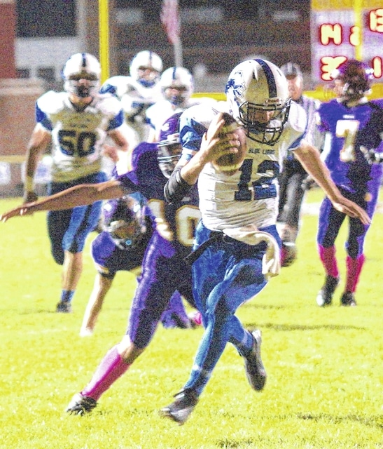 Washington Blue Lion quarterback C.J. Taylor (12) tries to avoid being tackled by McClain's Darius White (10) during an SCOL game at McClain High School in Greenfield Friday, Oct. 16, 2015. Also pictured for Washington is Trevor Hicks (50).