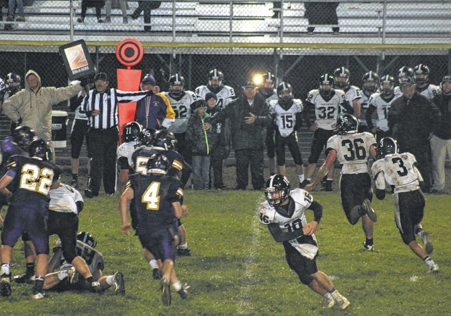 On a cold, rainy, windy night at McClain High School, Miami Trace's Larry Jackson (3 at right) carries with Baley Allen (36) out in front to block and quarterback Austin Lovett (16) faking the run in the opposite direction. Pictured for McClain are Randall Mischal (22) and Gabe Adams (4).