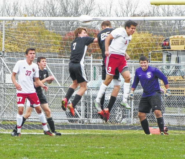 Three players go air born for the ball during a Division II Sectional soccer match featuring Miami Trace at Circleville High School Saturday, Oct. 24, 2015. Pictured for the Panthers (l-r); Nicholas Elrich (standing behind No. 37), Preston Huff (7), Matt Fender (25) and goalkeeper Tim Kinzler (5).
