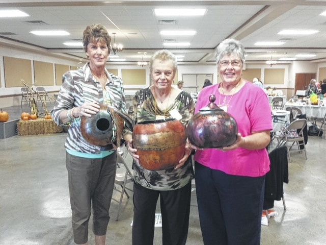 The Ohio Association of Garden Clubs Region 16 held its fall meeting Thursday at the Mahan Building on the Fayette County Fairgrounds. Pictured here (L to R): Carol Davidson, from Wilmington Garden Club, regional director Linda Morgan and Pat Parsons, from the Fayette Garden Club, all hold gourds made by the main speaker for the event.