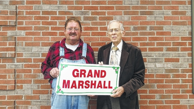 2015 Christmas Parade Grand Marshal Johnny Peters (left) beams as he hears the news from 2014 honoree Bill Boylan.