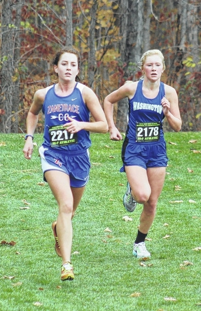 Washington High School sophomore Maddy Garrison, above, right, runs alongside junior Ivy Beam of Zane Trace during the Division II Regional cross country meet Saturday, Oct. 31, 2015 at Pickerington North High School. Garrison placed 39th out of 122 runners in a time of 20:57.7.