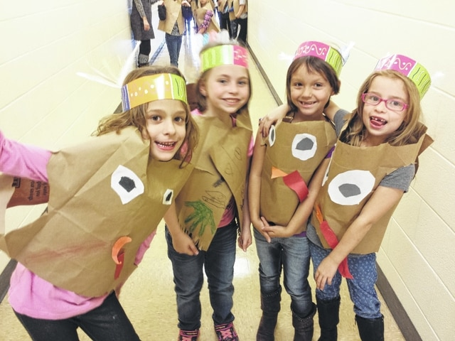 Volunteers help serve hungry Miami Trace Elementary students a Thanksgiving feast on Monday at the school. These students dressed as turkeys to show their Thanksgiving cheer.
