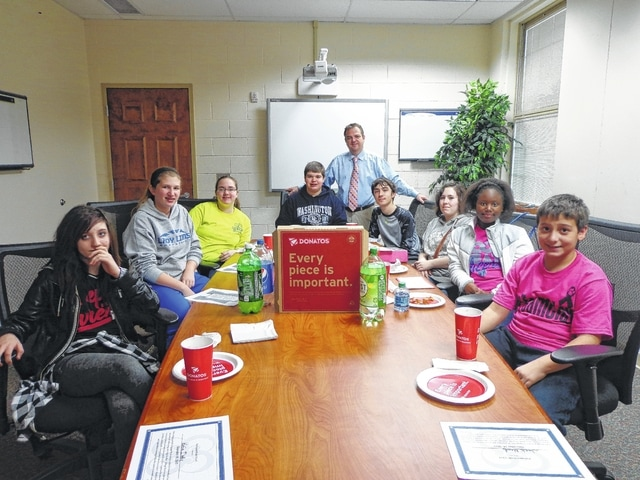 "Donatos recently provided pizza to these students at Washington Middle School as they celebrated ""Pizza with the Principals."" This is in appreciation for their selection as Students of the Month for December. They are chosen by their teachers because of the outstanding example they set for their peers in such areas as academic effort, good work ethic, kindness to others, and service to their school. Pictured from left: Katia Detty, Samantha Sever, Macy Miller, Trevor Minyo, (Mr. Montgomery, assistant principal) Jordan Carr, Mackenzie Bates, Davionna Hudson-Young and Jack Mead."