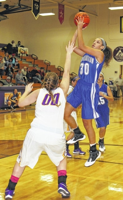 Washington freshman Hannah Haithcock (30) puts up a shot over McClain junior Beth Montgomery (00) during an SCOL game at McClain High School Wednesday, Dec. 9, 2015.