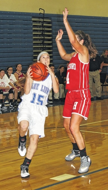 Washington freshman Kassidy Hines (15) takes the ball to the basket while being guarded by Hillsboro sophomore Natalie Sullivan during an SCOL game at Washington High School Saturday, Dec. 12, 2015.