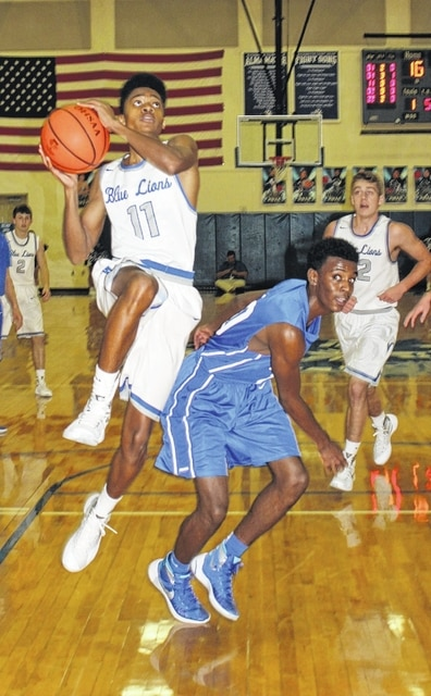 Washington Blue Lion junior Kenny Upthegrove (11) takes the ball to the basket during an SCOL game against the Chillicothe Cavaliers Friday, Jan. 15, 2016. Also pictured for the Blue Lions are Cameron Eckles (right) and Jarett Patton (back, left).