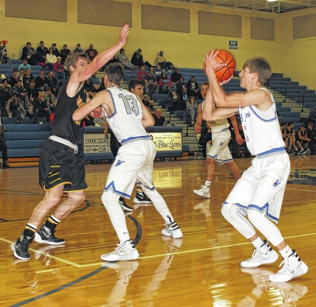 Washington Blue Lion senior Max Knisley sets for a long-range three-point shot attempt behind a screen from junior Griffin Shaw during a non-league game against Springfield Shawnee Tuesday, Feb. 9, 2016 at Washington High School.