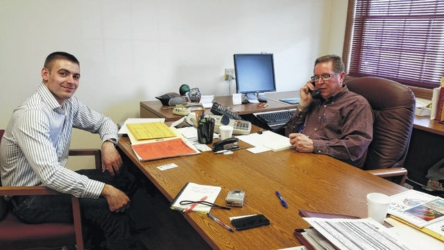 Sharing the Print Shop's owner's desk is Andy Daniels on the left and Jim Davis on the right.