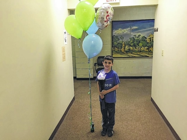 "Ian Sanchez, now 10, received a heart transplant when he was only 3-months-old. He continues to thrive and his life was celebrated Wednesday during a presentation at the Washington C.H. BMV. Here, he holds the ""Torch for Life."""