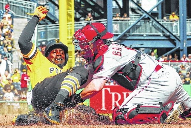 Pittsburgh Pirates' Andrew McCutchen, left, scores ahead of the tag by Cincinnati Reds catcher Tucker Barnhart during the eighth inning of a baseball game in Pittsburgh, Sunday. The Reds won in 11 innings, 6-5.