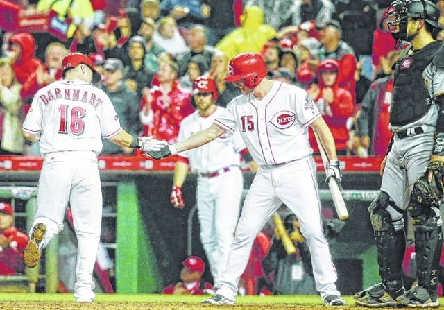 Cincinnati Reds' Tucker Barnhart (16) celebrates with Jordan Pacheco (15) after hitting the go-ahead home run off Pittsburgh Pirates starting pitcher Jonathon Niese in the seventh inning of a baseball game, Monday in Cincinnati. The Reds won 3-2.