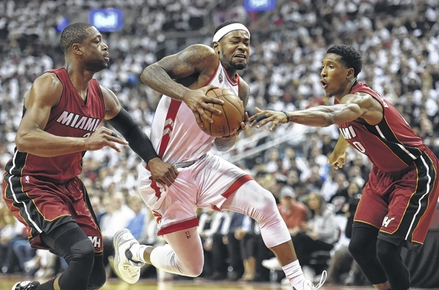 Toronto Raptors' Terrence Ross, center, drives to the net between Miami Heat's Dwyane Wade, left, and Josh Richardson during the first half of Game 7 of the NBA basketball Eastern Conference semifinals in Toronto, Sunday.