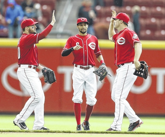 Cincinnati Reds outfielders, from left, Tyler Holt, Billy Hamilton, and Jay Bruce celebrate their 7-4 win over the San Francisco Giants on Wednesday in Cincinnati. Zack Cozart, Brandon Phillips and Eugenio Suarez hit homers in the Reds' five-run second inning as the Reds beat Jake Peavy for the first time and avoided a series sweep.