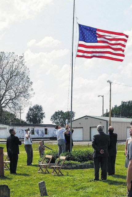 Ed Fisher and Amy Jackson raising the flag at Old Washington Cemetery.