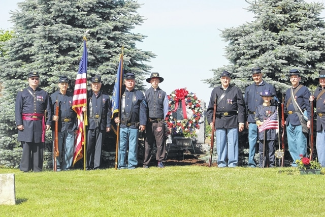 The Village of Bloomingburg held a Cemetery Memorial Service Monday sponsored by the Bloomingburg Masonic Lodge. Members of the Henry Casey Camp No. 92, Sons of Union Veterans of the Civil War and Commander Robert Grim are pictured standing with the Memorial wreath at the all-Veterans Dedication monument.