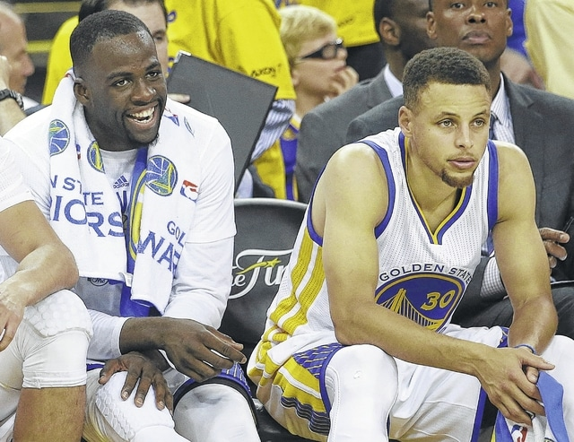 Golden State Warriors forward Draymond Green, left, smiles while sitting next to guard Stephen Curry during the second half of Game 2 of basketball's NBA Finals against the Cleveland Cavaliers in Oakland, Calif., Sunday.