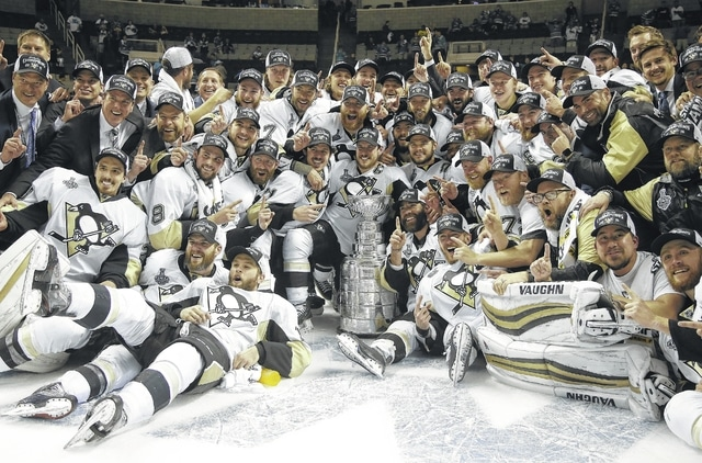 Pittsburgh Penguins players and coaches pose for photos with the Stanley Cup after Game 6 of the NHL hockey Stanley Cup Finals against the San Jose Sharks in San Jose, Calif., Sunday. The Penguins won 3-1 to win the series 4-2.