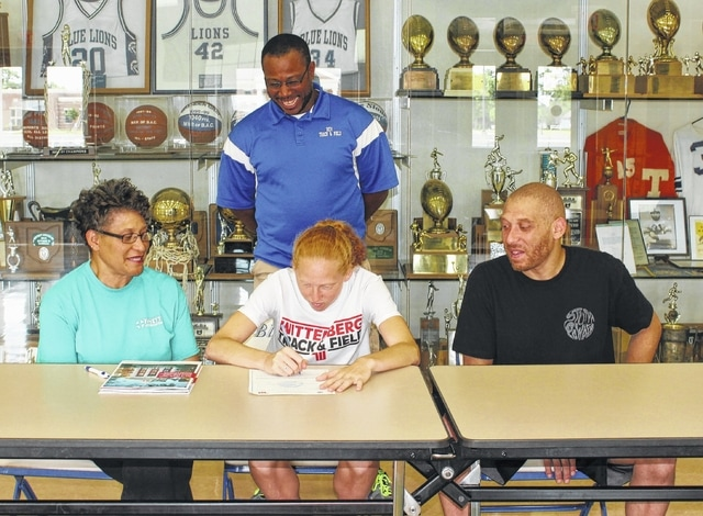 Recent Washington High School graduate Alexis Gray, seated, center, on Wednesday, June 15, 2016, signed a letter of intent to attend Wittenberg University where she will continue her education and her athletic career running track and cross country for the Tigers. She is flanked by her grandmother, Mary Gray and her father, David Gray and also joined by her high school track coach, Louis Reid.