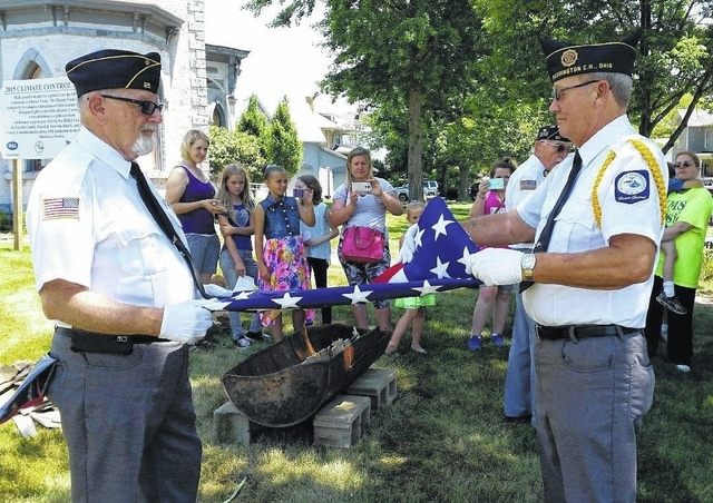 Pictured are Honor Guard members Paul Sands, left, and John Mason folding a flag as Edward Fisher reads the history of the 13 folds.
