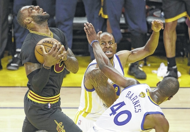 Cleveland Cavaliers forward LeBron James, left, shoots against Golden State Warriors forward Harrison Barnes (40) and forward Andre Iguodala during the first half of Game 5 of the NBA Finals on Monday in Oakland, Calif.