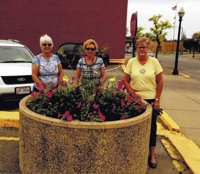 Deer Creek Daisy club members planted a large pot of flowers, located downtown, in the public parking lot on Fayette Street. Pictured (L to R): Julie Schwartz, Connie Lindsey and Judy Gentry. This was the garden club's community project. The flowers were donated by McClish's Plants Plus.