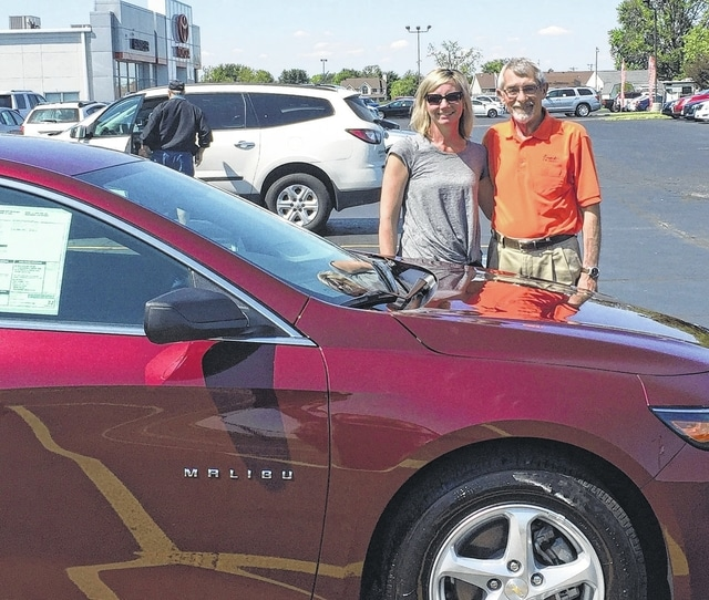 Sid Charles, sales manager at Gusweiler GM Center, with Holly Cottrill, Hospice of Fayette County fundraising coordinator, stand in front of the 2016 Chevy Malibu that was in the contest.