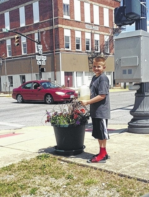 The 4-H Fun Bunch participated in the Flower Pot program, sponsored by the Fayette County Master Gardeners. The club sponsored a beautiful pot of flowers that is currently located in Jeffersonville. Pictured is the flower pot, sponsored by the club and club member, Nicholas Farrens, watering the plants.