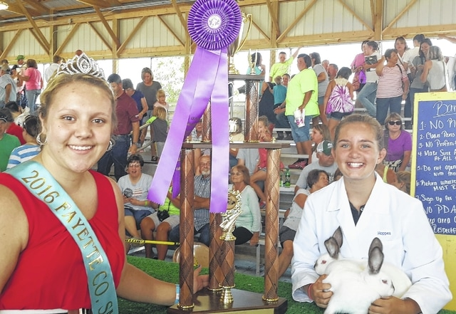 Kassidy Hoppes (right) was presented with the grand champion trophy by Macy Detty (left) for the Jr. Fair Rabbit Meat Pen Show.