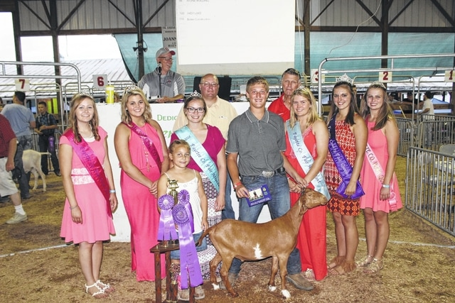 Ethan Steele's grand champion dairy meat goat sold for $1,225 Thursday at the Fayette County Junior Fair Dairy Goat Sale. Pictured with Steele (center) are buyers and fair royalty: (front) Fair Attendant Virginia Schappacher, Small Animal Queen Marissa Sheets, Fair Attendant Ginna Climer, Fair Attendant Alexis Schwartz, Fair Queen Bethany Reiterman, Pork Queen Hannah Casto, (back) Nathan Steele of Hidy Pay Lake and Bolen Construction, and Wayne Arnold of A-One Building.