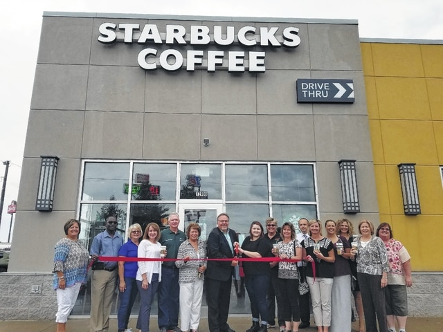 Starbucks Store Manager Ashley Horning cuts the ribbon Monday to officially open Starbucks Coffee Shop at U.S. 35/ I-71. Pictured (L to R): Chamber Director Whitney Gentry, Fayette County Economic Development Director Godwin Apaliyah, Chamber board president Merleen Van Dyke, Ambassador Julie Bolender, Jeffersonville Mayor Bob Kinzer, Jeffersonville Council Member Sue Burnside, Starbucks District Manager Brad Griffis, Horning, Ambassador Colleen Roundhouse, Ambassador Kathy Patterson, Tanger Outlets Assistant Manager Andy Gibson, Chamber board member Holly Cottrill, Ambassador Mekia Rhoades, Tanger Outlets Manager Kristin Hauer, Ambassadors Ruth Ann Ruth and Robin Beekman.